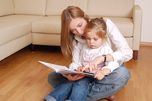 young mom reading her little daughter storybook on a floor